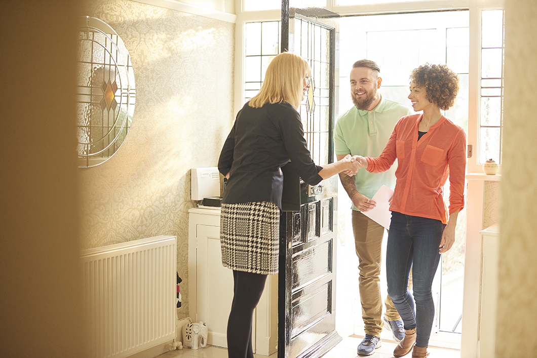 a young couple view a property guided by an estate agent. They are entering the hallway of house and chatting about the paperwork that they are holding .